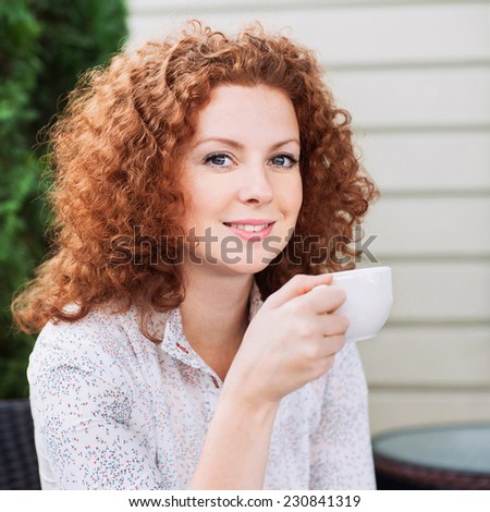 Pretty young woman sitting in a cafe with a cup of coffee - stock photo