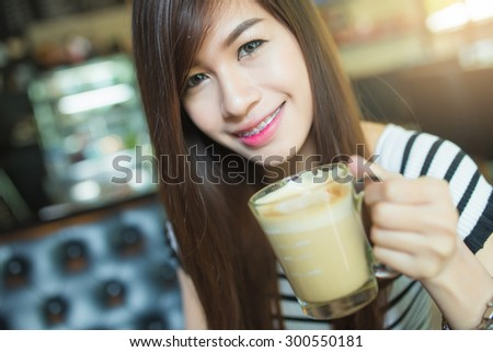 pretty young woman sitting in the cafe with a cup of coffee