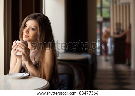 pretty young woman sitting in the cafe with a cup of tea - stock photo