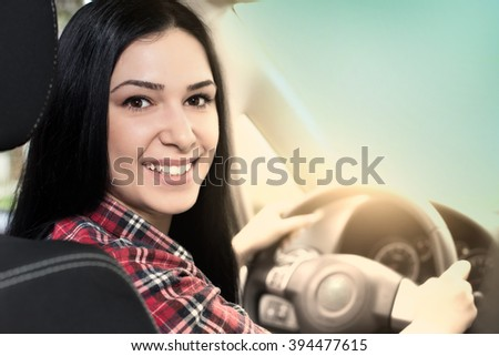 Pretty young woman sitting in the car on diver's place and looking back over the shoulder - stock photo