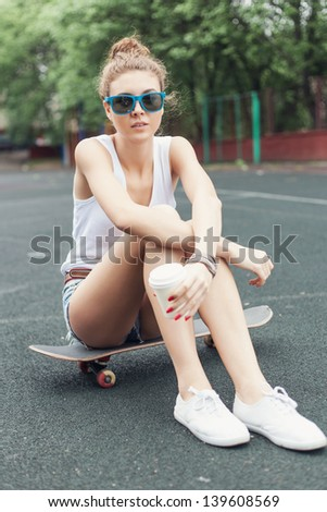 Pretty young woman sitting on a skateboard in the daytime, outdoors - stock photo