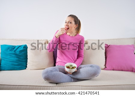 Pretty young woman sitting on a sofa with her legs crossed and eating healthy salad.