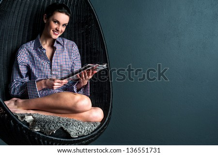 Pretty young woman sitting on bubble chair and reading magazine. - stock photo