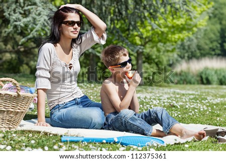 Pretty young woman sitting on grass with her son