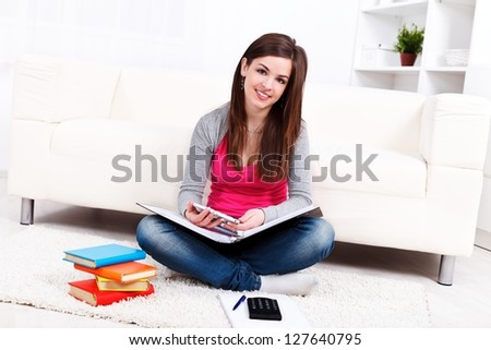 Pretty young woman sitting on the floor and studying