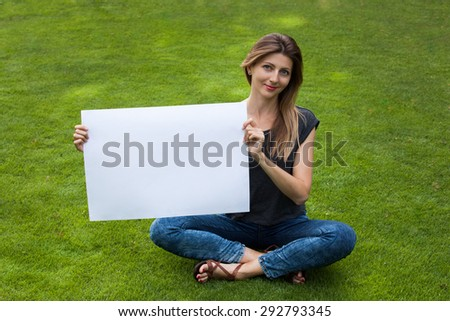 Pretty young woman sitting on the grass with white board - stock photo