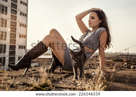 pretty young woman sitting on the roof with a cat, focus on cat - stock photo