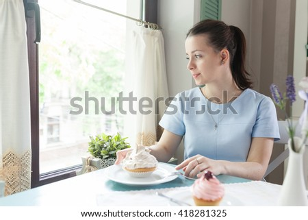 Pretty young woman sitting on the window sill and drinking coffee. Dreamy european girl enjoying breakfast looking through the window. Beautiful girl smiling and holding a meringue cupcake. - stock photo
