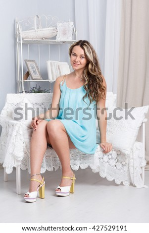 Pretty young woman sitting on vintage retro sofa couch