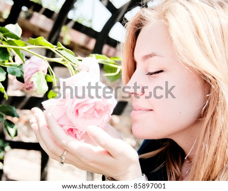 Pretty young woman smelling a rose - stock photo