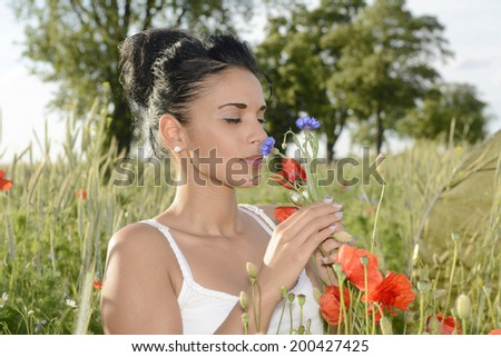 pretty young  woman smelling  poppy and cornflower  - stock photo