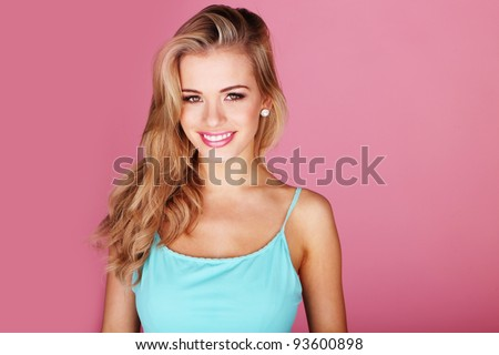 Pretty young woman smiling against a pink background - stock photo