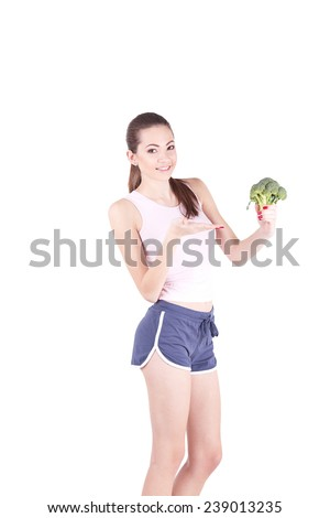 Pretty young woman smiling while holding some broccoli - stock photo