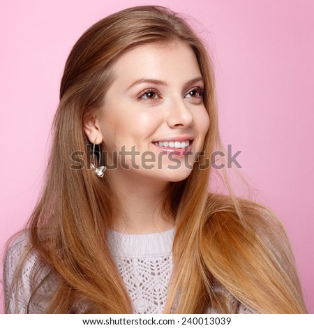 Pretty young woman smiling with her teeth at the pink background.  - stock photo