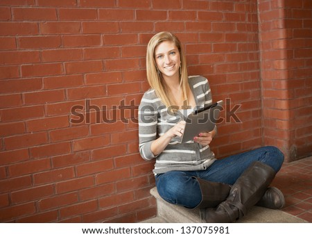 Pretty young woman smiling with tablet computer - stock photo