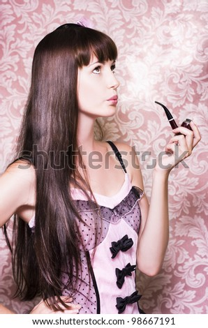 Pretty young woman smoking a pipe and looking pensively up at the sky as she indulges in pipe dreams and flights of fantasy - stock photo