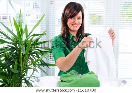 Pretty Young Woman Sorting Through The Laundry Basket - stock photo