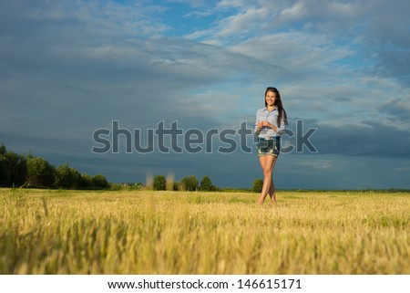 Pretty young woman stand in grass field
