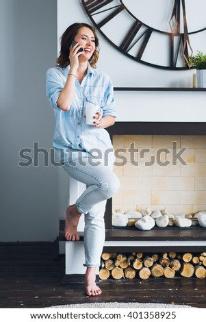 Pretty young woman standing near fireplace with coffee cup and talking on a cell phone - stock photo