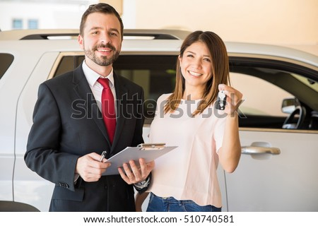 Pretty young woman standing next to a salesman at a dealership and holding the keys to her new car