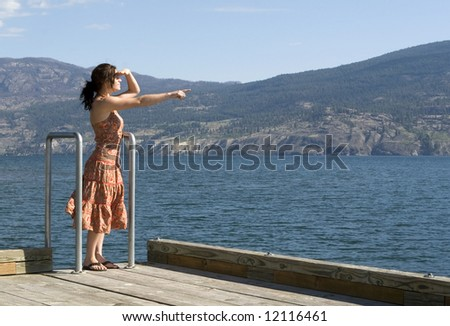 Pretty young woman standing on pier pointing to the distance, wearing summer dress. Lake and mountains in background.