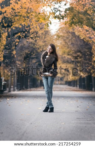 Pretty young woman standing outdoors. Attractive girl posing and wearing fur in a park,  autumn day - stock photo