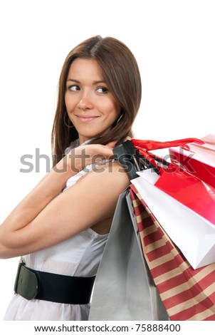 Pretty young woman standing sideways with shopping bags in hand slung over her shoulder on a white background - stock photo