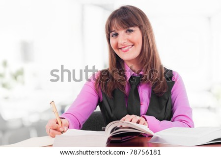 Pretty young woman studying in a class room - stock photo
