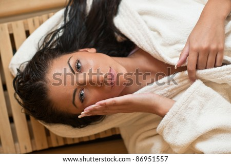 Pretty Young woman take a steam bath treatment at finish wooden sauna while wearing white towel - stock photo