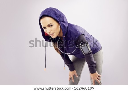 Pretty young woman takes a break after running looking at camera smiling. Female runner looking tired over grey background - stock photo