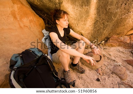 Pretty, young woman taking a break in the shade after doing some hiking. Active/Outdoor lifestyle concept.