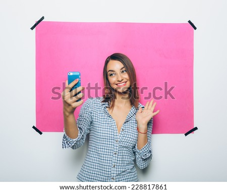 Pretty young woman taking picture with camera phone over pink background - stock photo
