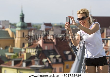 Pretty young woman taking pictures on his smartphone old european city from the observation deck. - stock photo