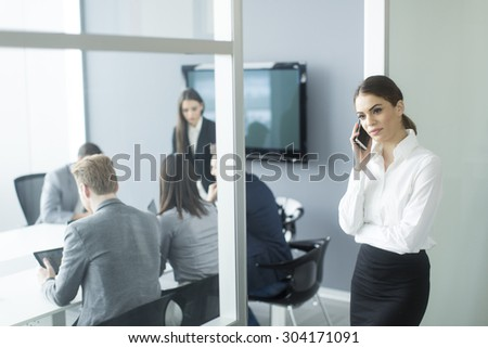 Pretty young woman talking on mobile phone in the office