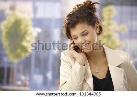 Pretty young woman talking on mobilephone outdoors, smiling happy. - stock photo