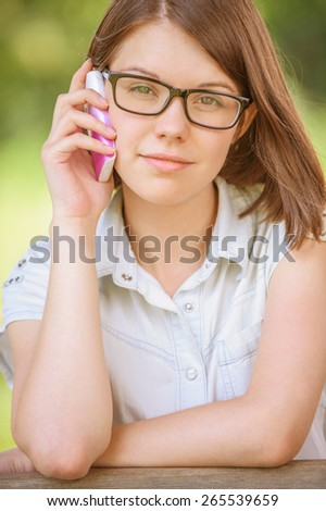 pretty young woman talking phone short hair wearing glasses background summer green park - stock photo