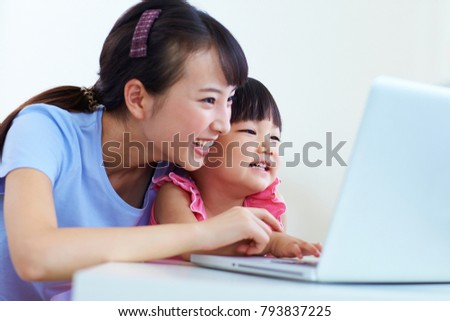 pretty young woman teaching little girl using laptop in home