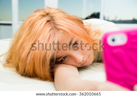 Pretty young woman, teenager lying cozy in bed holding pink mobile phone taking selfie. - stock photo