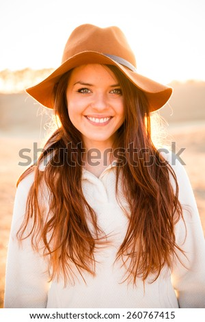 Pretty Young Woman - This is a portrait of a beautiful young woman back lit by a sunset. Shot in a warm color tone.  - stock photo