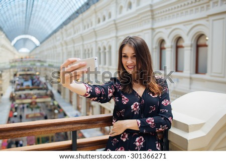 Pretty young woman tourist takes selfie in Instagram in Moscow, Russia