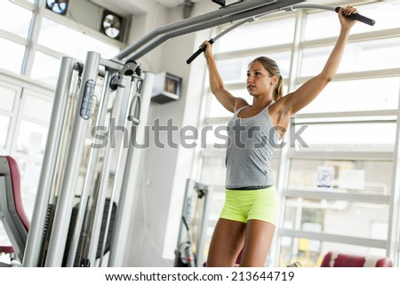 Pretty young woman training in the gym - stock photo