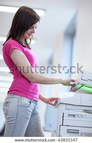 pretty young woman using a copy machine (shallow DOF; color toned image) - stock photo