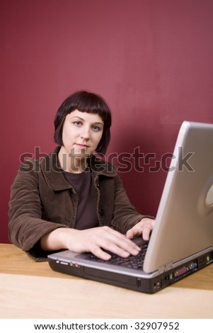 Pretty, young woman using a laptop in a home environment.
