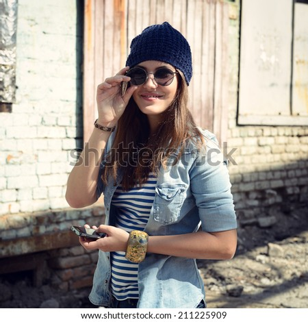 Pretty young woman using mobile phone and getting photos, outdoor. Toned. - stock photo