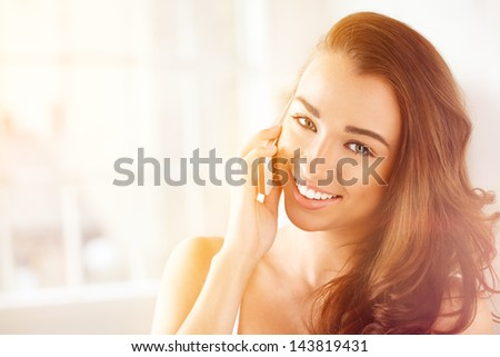 pretty young woman using mobile phone at home - stock photo
