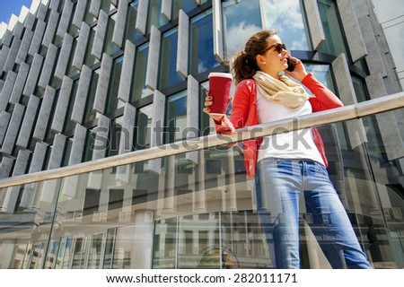 Pretty young woman using mobile phone holding coffe cup - stock photo
