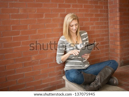 Pretty young woman using tablet computer studying - stock photo