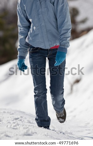 pretty young woman walking in deep snow on a sunny winter day