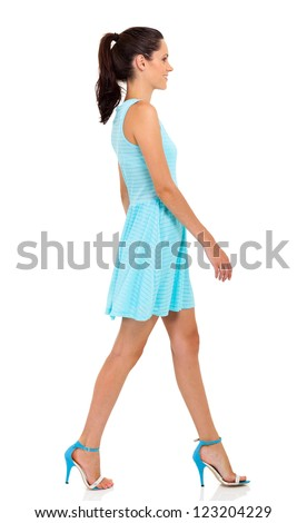 pretty young woman walking on white background - stock photo