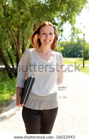 Pretty young woman walking with laptop under the hand - stock photo